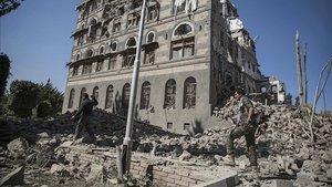 Dos rebeldes yemeníes inspeccionan las ruinas de edificios destruidos por los bombardeos en Saná