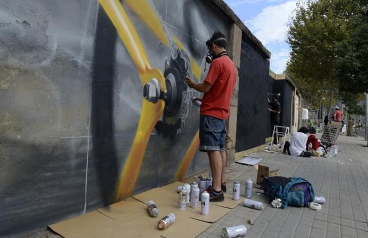 El artista callejero Flow trabaja en su grafiti en el paseo de la Circumval·lació.