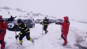 Unos militares tratan de liberar con palas los coches atrapados en la AP-6 por la nevada.