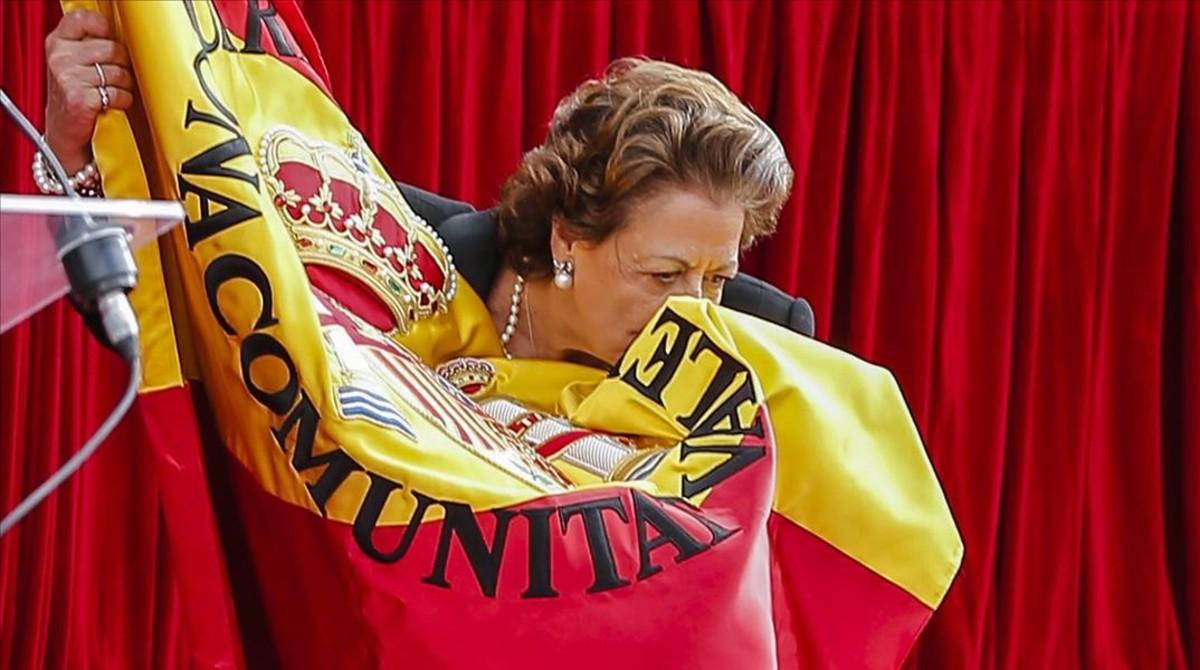 Besando la bandera española durante la festividad de la patrona de la Guardia Civil.