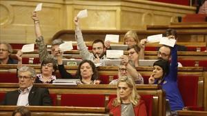 Los diputados de la CUP exhiben papeletas del eventual referéndum, en el debate del Parlament sobre los presupuestos.