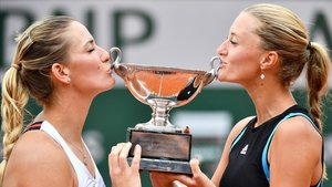 Kristina Mladenovic (derecha) y Timea Babos besan el trofeo de campeonas de dobles de Roland Garros.