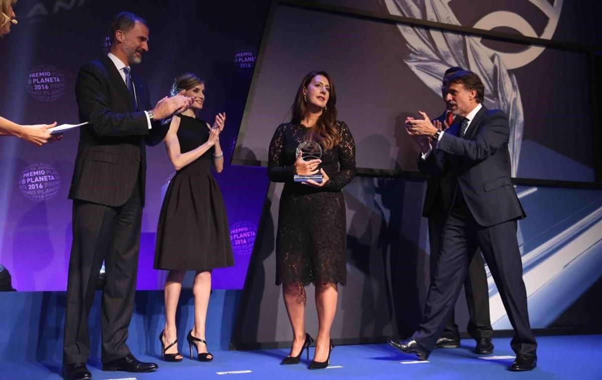 Dolores Redondo sostiene el premio ante los aplausos de los reyes de España y el presidente de Planeta.