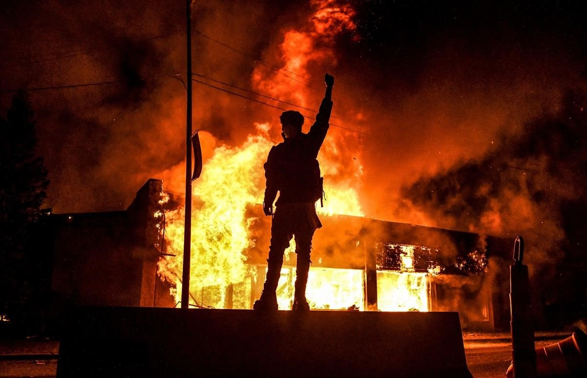Un manifestante, frente a un edificio en llamasdurante lamanifestación en Minneapolis.