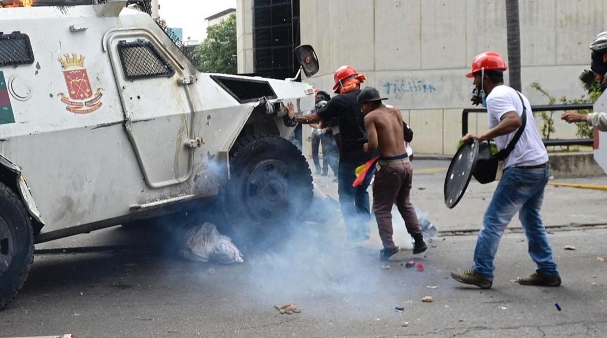 Un manifestante yace bajo una tanqueta policial en Caracas.