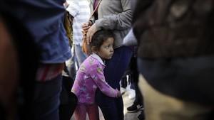 Una niña mexicana con su madre espera con otros inmigrantes en la fronterala respuesta a la solicitud de asilo político en EEUU.