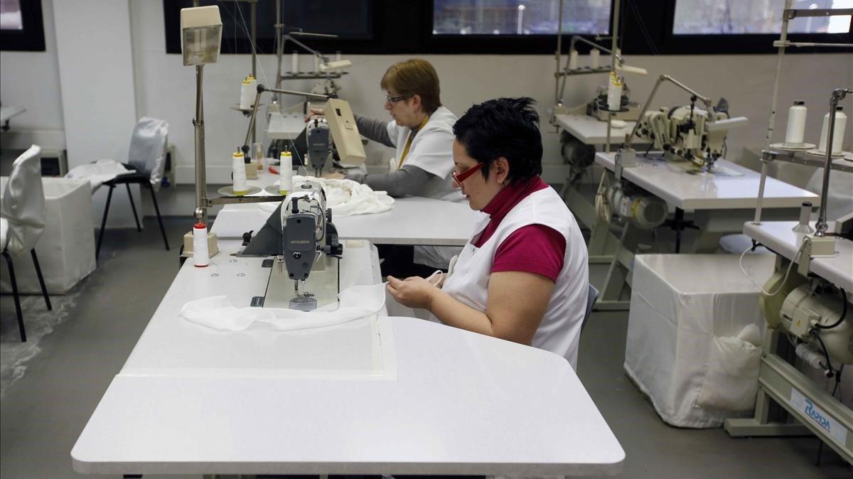 Mujeres trabajando en un taller de confección de vestidos de novia.