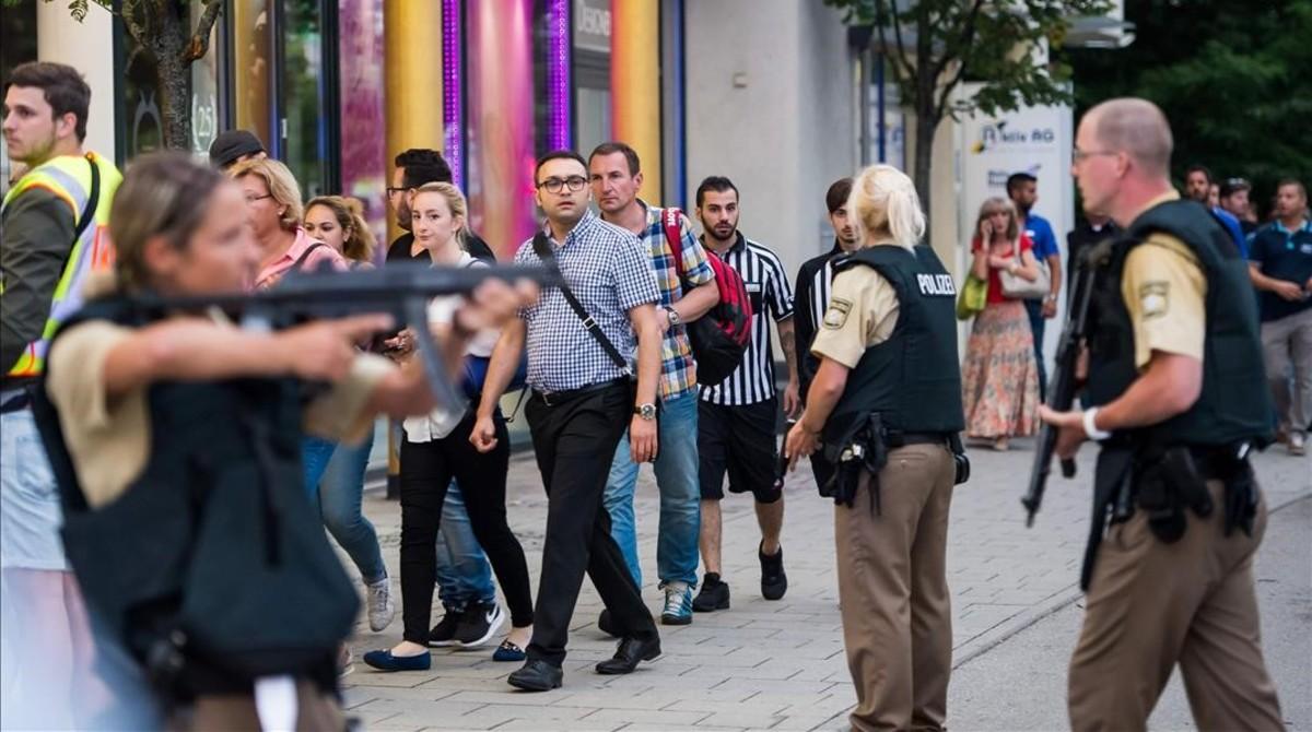 La policía evacúa a varias personas del centro comercial atacado en Múnich, este viernes.