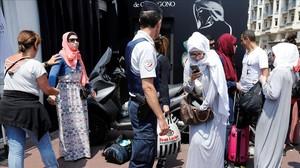 La policía francesa controla a unas mujeres antes del evento organizado en favor del burkini.