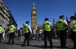 La policía londinense controla a los manifestantes anticonservadores en una marcha en la plaza del Parlamento, en el centro de Londres.