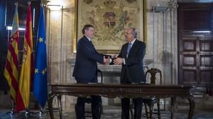 El presidente de la Generalitat valenciana, Ximo Puig, y el de la Fundació Bancària La Caixa, Isidre Fainé, firman un covenio de colaboración.
