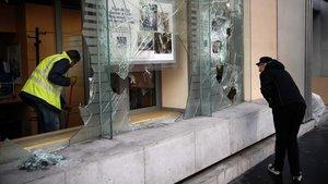 Un empleado limpia el interior de un banco de Parísmientras un vecino observa los destrozos.