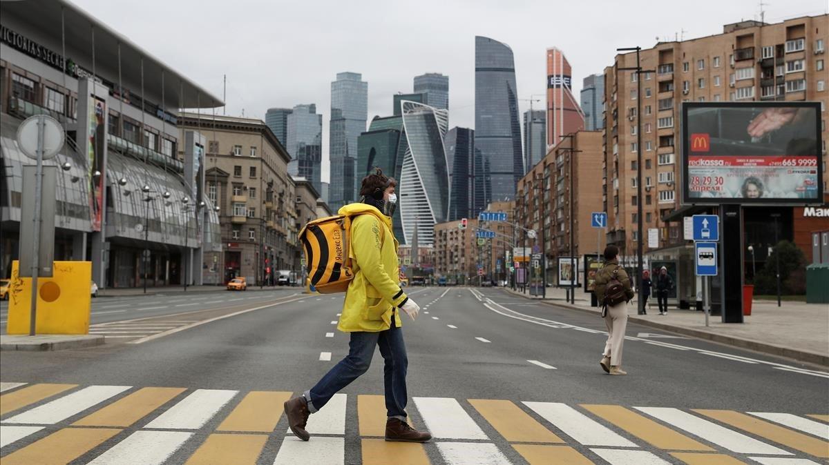 Un repartidor de comida a domicilio cruza una desierta calle de Moscú, este lunes.