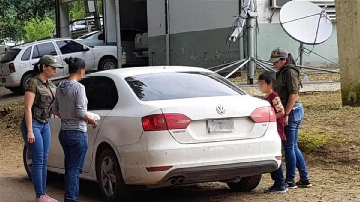La mujer argentina que fue explotada durante 32 años, con sudadera gris, a punto de entrar en una patrullaa junto a su hijo de 9 años.