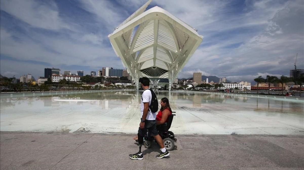 Una pareja con discapacidad pasa frente al Museo del Futuro, este martes en Río.