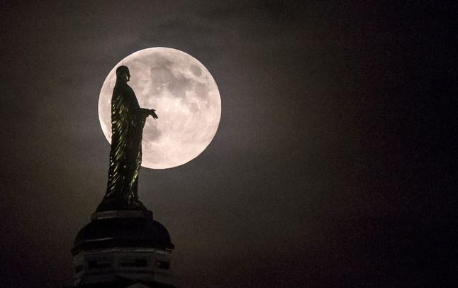 La silueta de una estatua de la Virgen María sobre la lluna llena, en Indiana (EEUU).