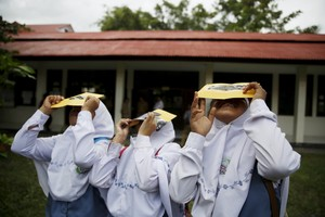 Students test their self-made filters and look at the sun after a joint workshop between the Hong Kong Astronomical Society and Indonesia's National Institute of Aeronautics and Space (LAPAN) at a high school in Ternate island, Indonesia, ahead of Wednesday's solar eclipse, March 7, 2016. REUTERS/Beawiharta