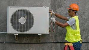 Un técnico revisa un aparato de aire acondicionado.