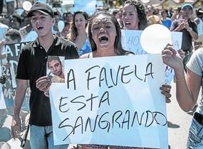 Una mujer participa en la 'marcha por la paz' en la favela Alemao tras la muerte de un niño por la policía.