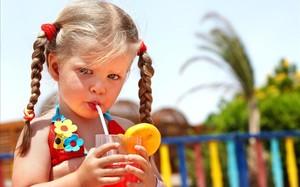 Una niña en bikini se toma un refresco.