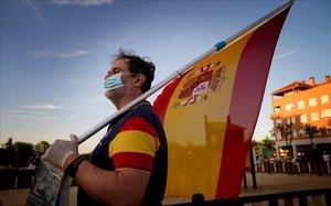 Un manifestante porta la bandera de España el miércoles 20 de mayo en una protesta en Las Rozas (Madrid).