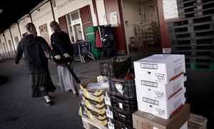Soportales de los almacenes del Banco de Alimentos en Mercamadrid. Dos jóvenes monjas acarrean un palé de comida para su entidad benéfica.