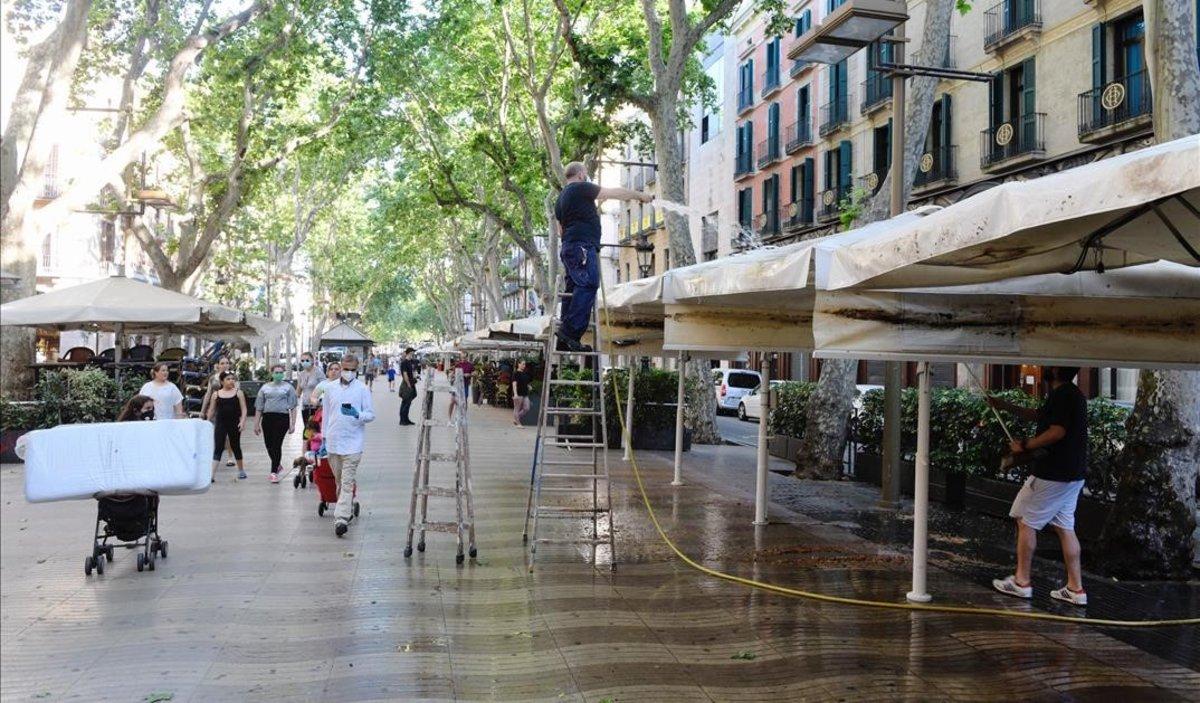 Unos trabajadores limpian los toldos de una terraza en La Rambla de Barcelona.