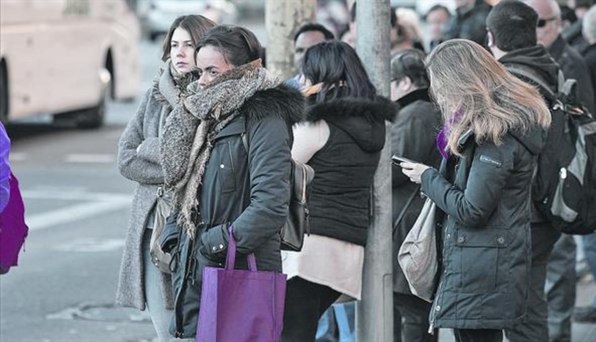 Usuarios del autobús, en una mañana de frío en Barcelona.