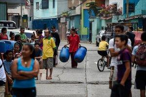 Vecinos del barrio de Petare, en Caracas, hace cola para adquirir agua.