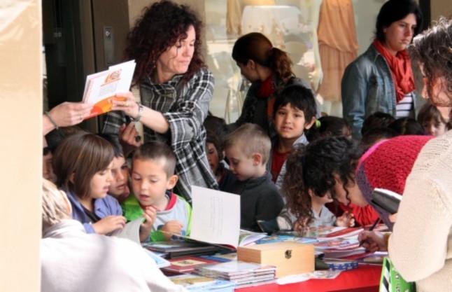 Un gurpo de niños mira los libros de una parada, en Vic.