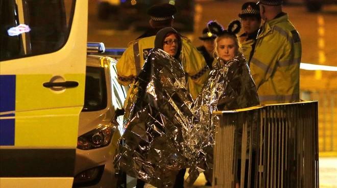 Dos chicas son atendidas por los servicios de emergencia a las afueras del Manchester Arena.