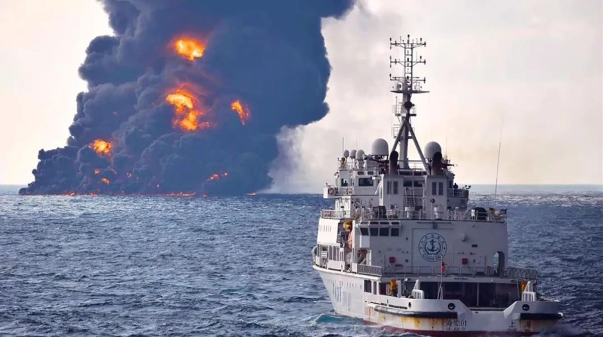 Una embarcación de rescate y a lo lejos el petrolero Sanchi en llamas.