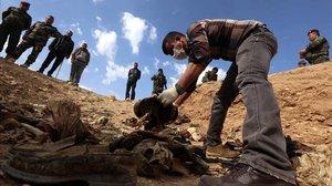 Integrantes de la minoría yazidí revisan restos de víctimas del EstadoIslámico, en el noroeste de la zona de Sinjar, en Irak.