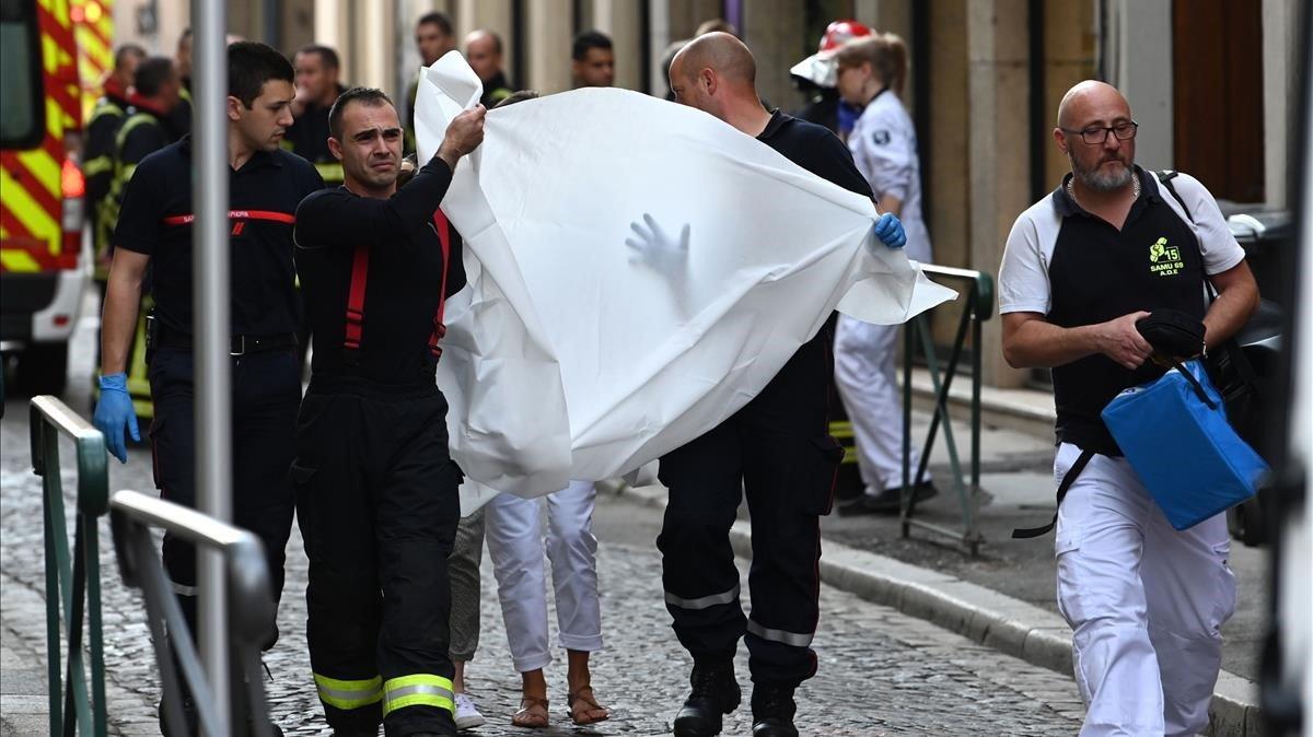 Personal sanitario trasladan a una víctima de la explosión.