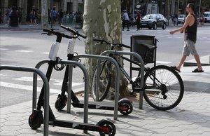 Patinetes de una de las empresas que desoyen la ordenanza municipal, aparcados en el paseo de Gràcia.