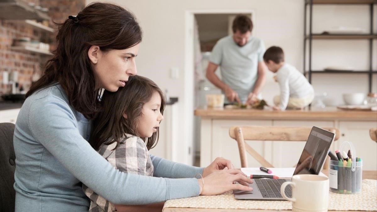 Una mujer trabajando en su casa mientras atiende a su hija.