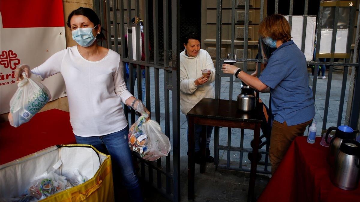 Reparto de alimentos a personas necesitadas en la iglesia de Santa Anna de Barcelona.