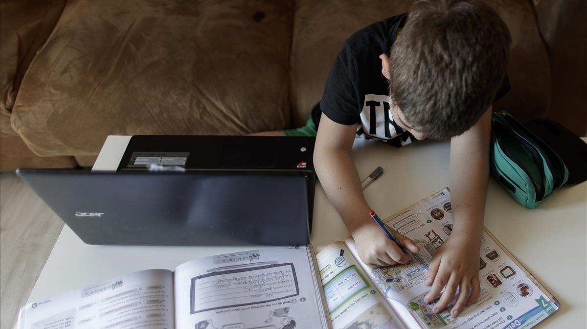 Una alumno de primaria hace los deberes con la ayuda de un ordenador.