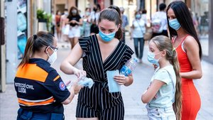 Una agente de Protección Civil distribuye mascarilas en el Eix Comercial de Lleida, este lunes.