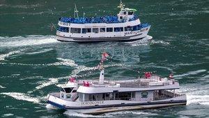 Un barco con turistas canadienses (de rojo) y de EEUU (de azul), en las cataratas del Niágara.