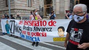 El padre de Pedro Álvarez, en primer plano, delante de una pancarta de apoyo, ayer en la puerta de la Audiencia de Barcelona.