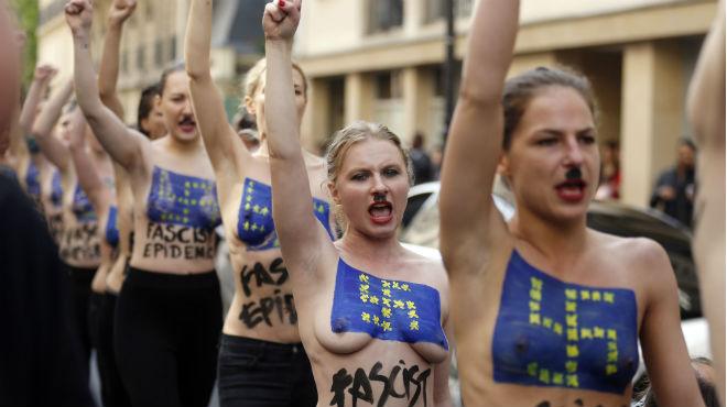 Las activistas desfilan por las calles de París con esvásticas y la bandera de la UE pintadas en el pecho.