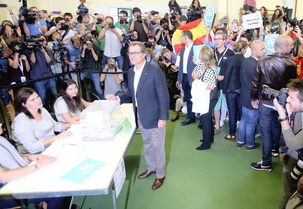 Artur Mas deposita su voto. Tras él, un joven ha desplegado una bandera española.