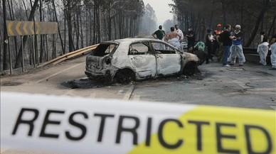 Bomberos y forenses junto a un vehiculo calcinado en la carretera de Castanheira de Pera y Figueiro dos Vinhos