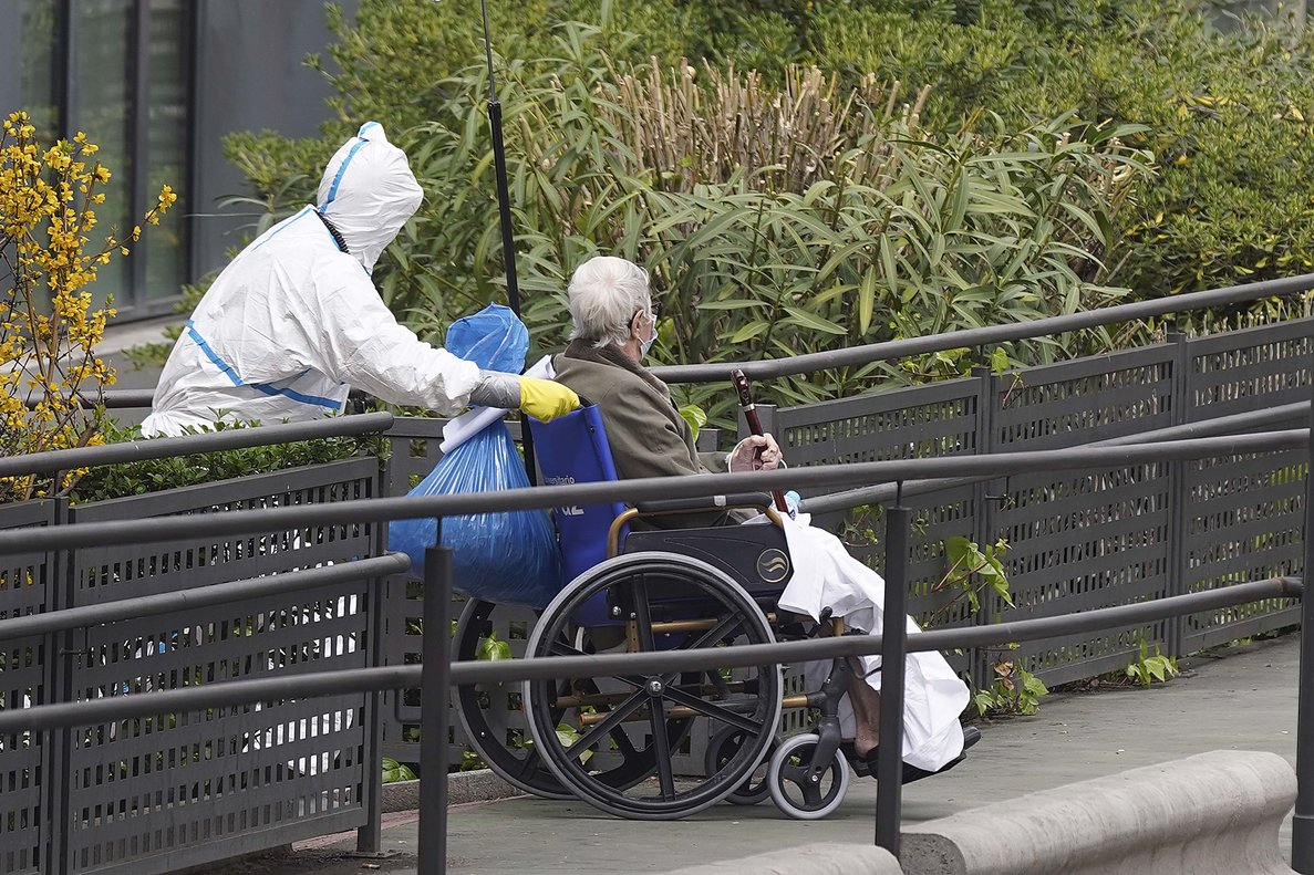 Dos enfermeros trasladan a un enfermo de coronavirus del hospital La Paz de Madrid.