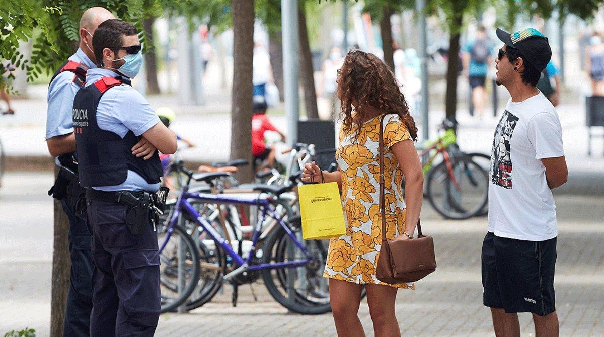 Dos agentes de los Mossos d'Esquadra advierten a unos transeúntes de la obligatoriedad de llevar mascarilla, en Barcelona el 10 de julio.