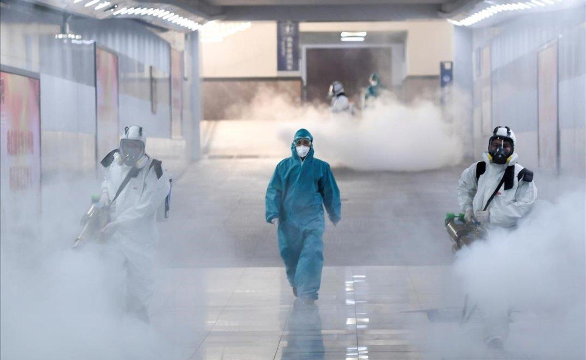 Un grupo de voluntarios desinfectan una estación de tren en Changsha, China, ante posibles contagios de coronavirus.