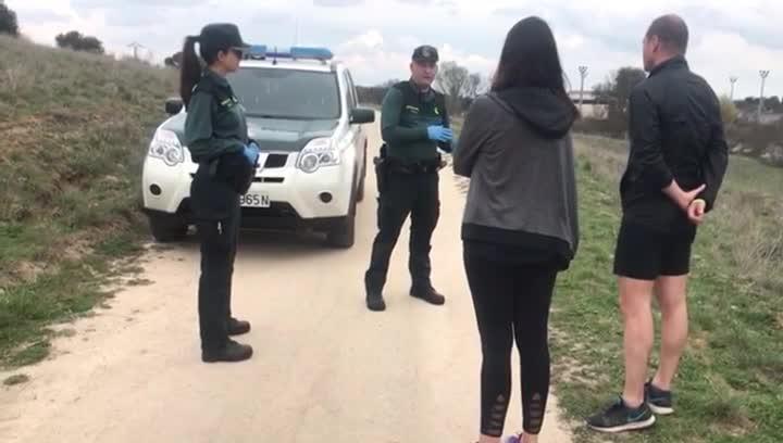 Guardias civiles informan a dos paseantes -a metro y medio de distancia- de que están violando la orden confinamiento por la epidemia de coronavirus.