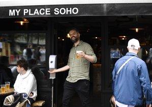 Un hombre sale con una cerveza en la mano de un pub en Londres.