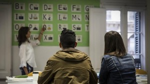 Mireia Escobar, coordinadora del proyecto de jovenes Ta-Axira, junto a un joven migrante y su profesora Constanza en una de las clases de castellano.